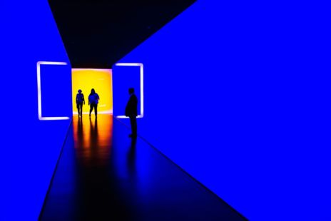 Two Silhouettes Walking Through A Blue Corridor
