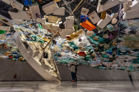 Visitors In A Gallery Walking Under Artwork Made Of Recycled Materials