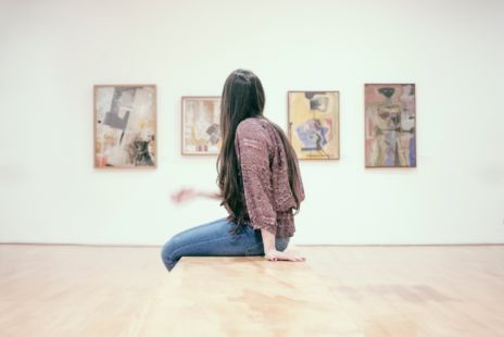 Woman In Gallery Looking At Abstract Paintings