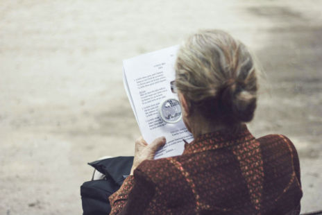 Woman Reading A Document Using A Magnifying Glass