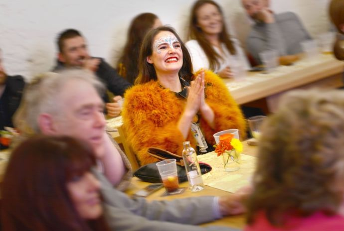 A woman smiling and clapping in a crowded room.