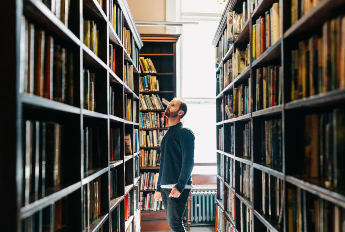 Man Looking At Books In Library