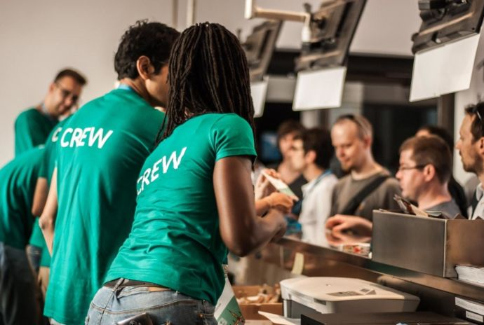 Staff At Ticket Desk With Green T Shirts That Say Crew On Them