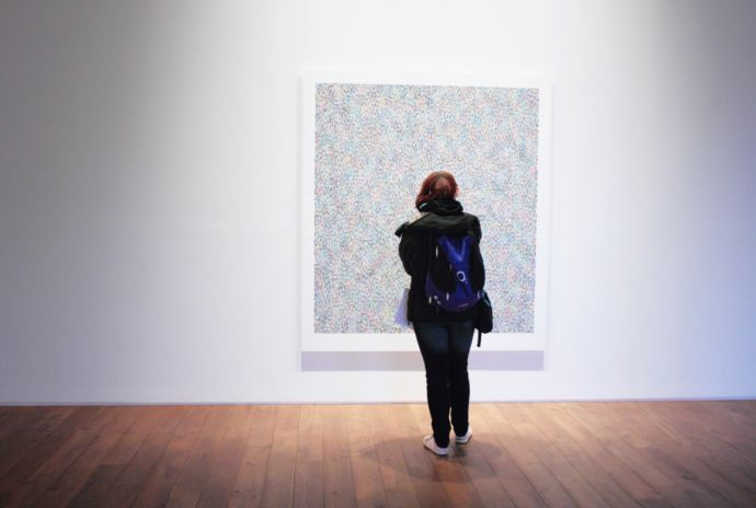 Woman looking at a painting in an art gallery