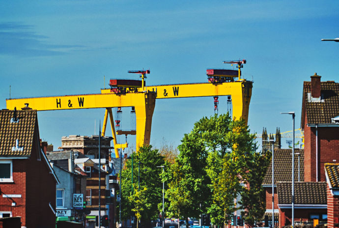 Yellow Industrial Cranes Behind View Of Redbrick Houses
