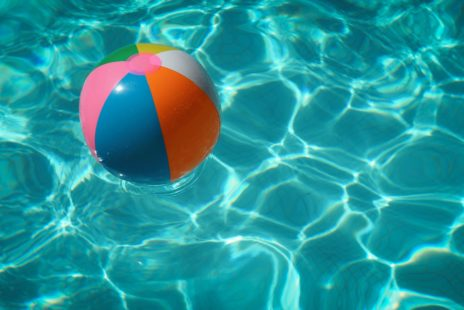Water of a swimming pool with sun reflections and a plastic ball