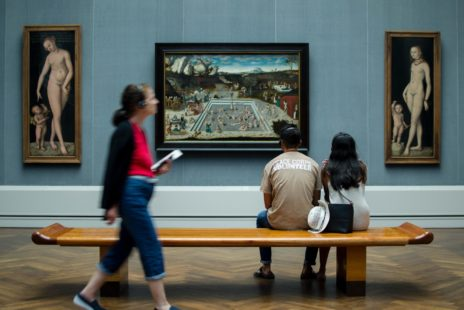 A couple is sitting on a bench in a museum, looking at painting. A woman with headphones is walking behind them, looking at the same paintings.
