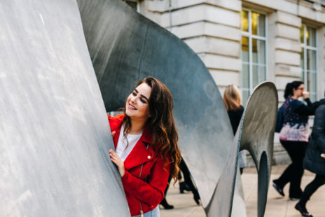 White girl with long hair is standing, smiling, behind an outdoor sculpture in front of the Ulster Museum