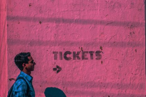 Man walking by tickets sign