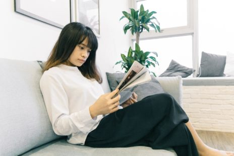 Woman reading magasine sitting on a couch