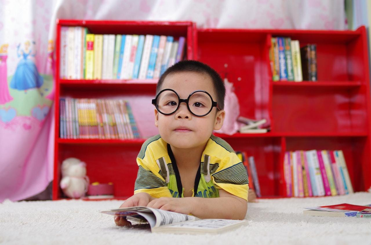 Child in library reading a book