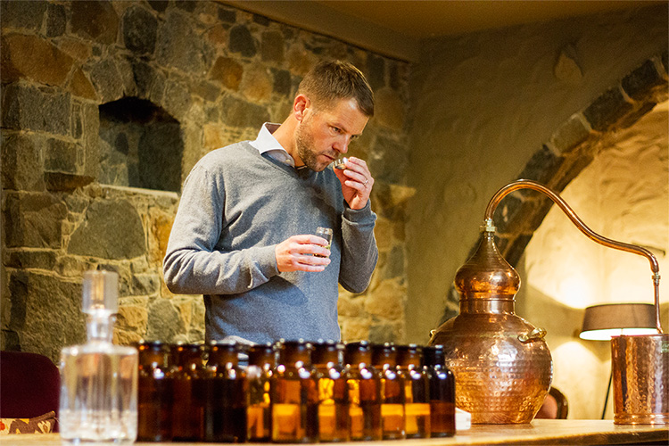 Wheadon's Gin Founder Luke Wheadon sniffing jars of botanicals