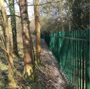 Caption: Green powder-coated steel palisade fencing