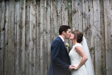 cornish vineyard wedding bride and groom kiss - image by ashley hampson