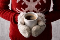 Woman hands in cute christmas mittens holding a cup of coffee or cocoa with a candy cane