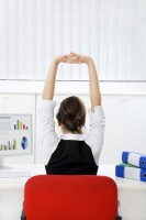 Rear view of young businesswoman sitting at desk stretching. Copy space