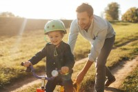Photo of a young boy who is learning to ride a bicycle with a little help from his father