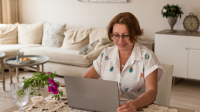 Nainen istuu kotona laptop pöydällä
