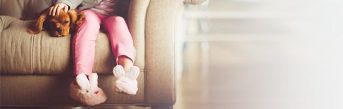 Girl on sofa with pet dog