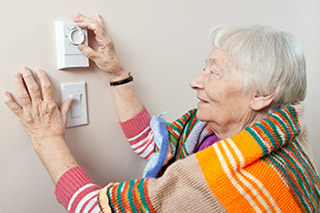 pensioner adjusting thermostat