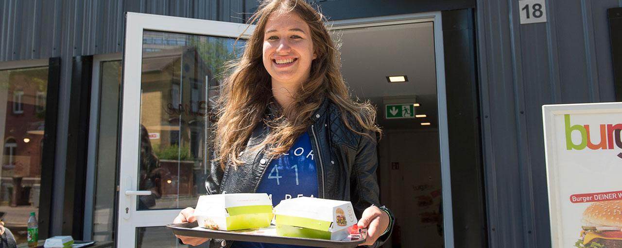Abbildung einer jungen, fröhlich wirkenden Frau, die Burger auf einem Tablett trägt