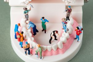 Tiny characters working on teeth