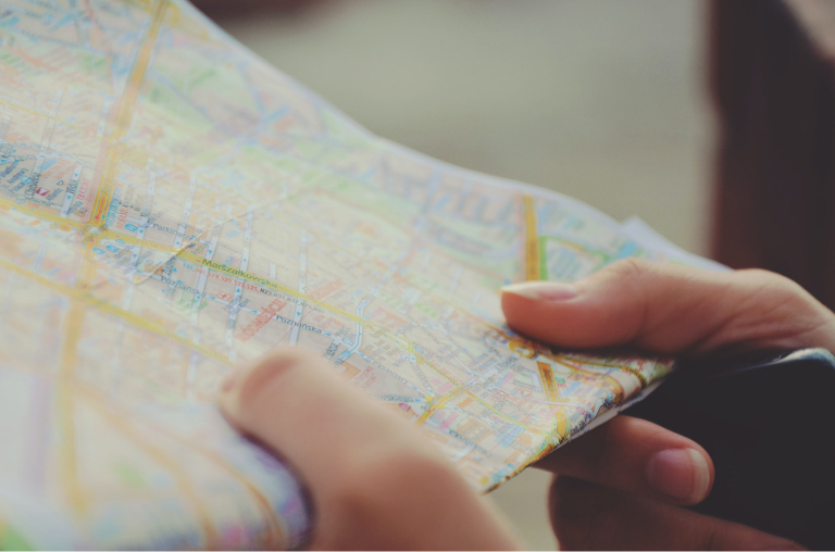 A lady holding a map looking at an area.