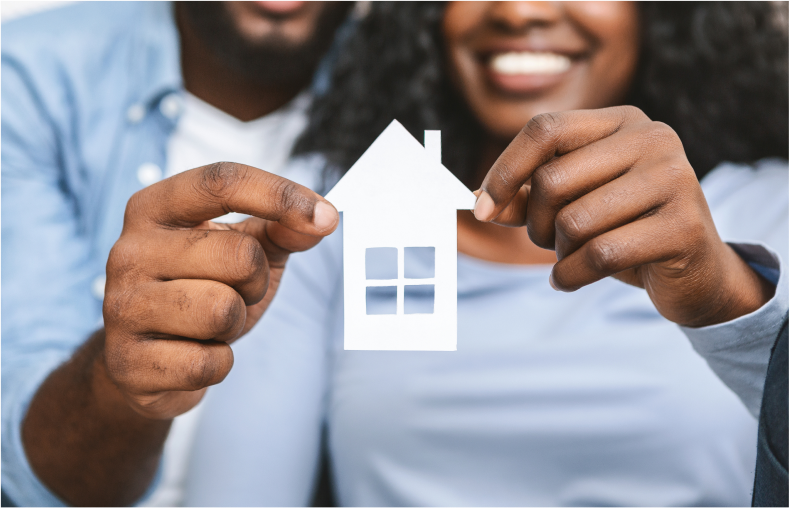 Excited couple hold up a white paper house.