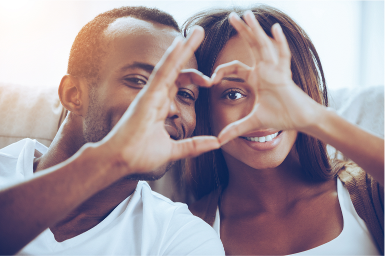 A Couple making the shape of a heart with their hands.