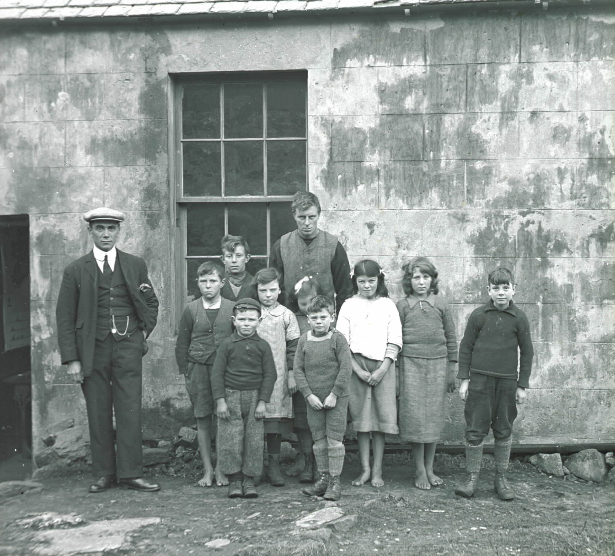 Fig. 9: Glass plate negative of barefoot school children outside the school building, #99 © National Trust for Scotland, St Kilda