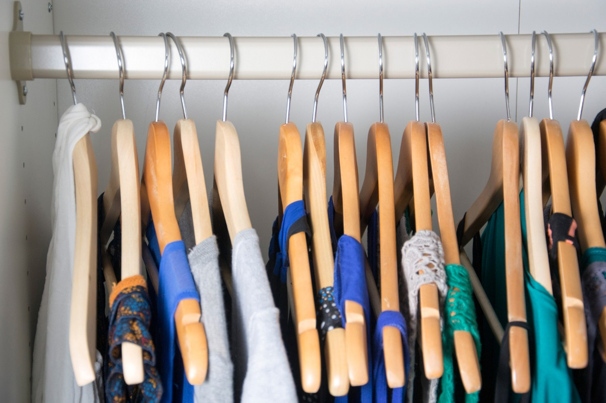 Summery seasonal clothing items hanging on wooden hangers in a closet