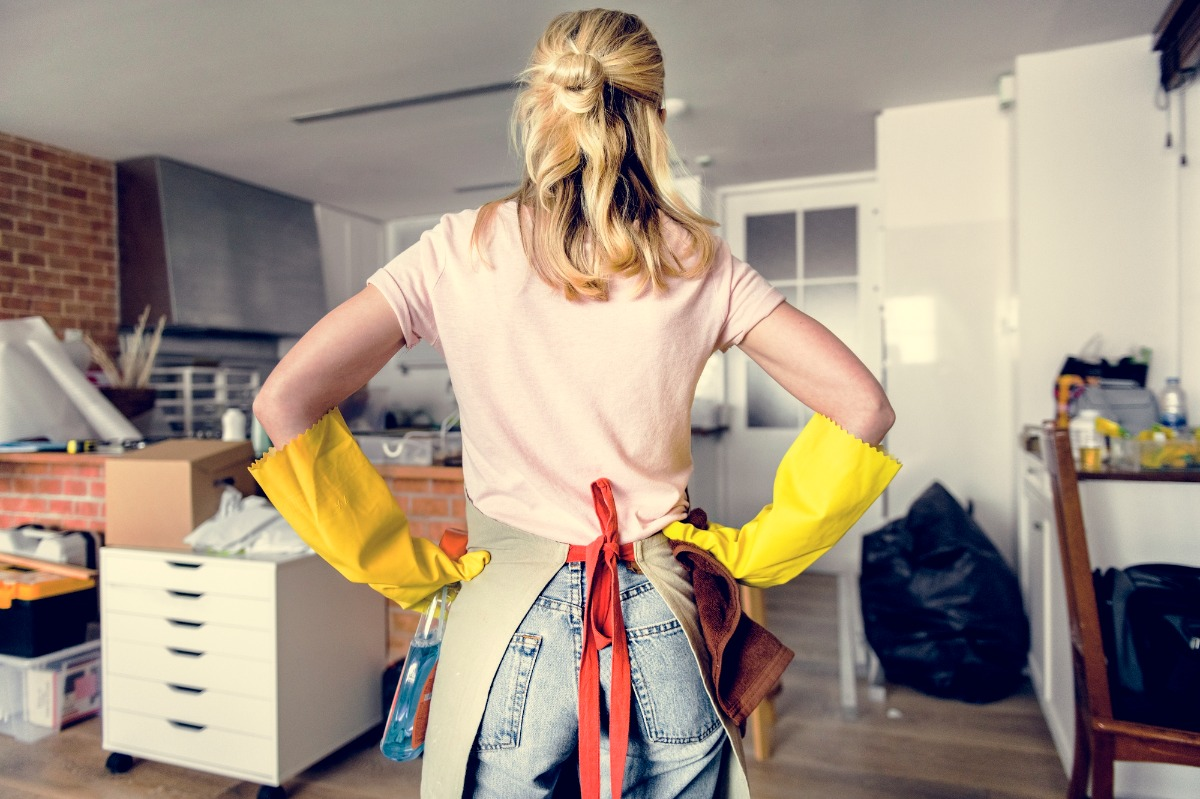[A woman standing with her hands on her hips facing a very messy kitchen and considering the benefits of decluttering]
