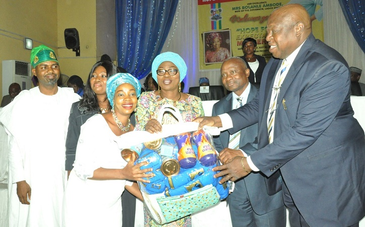 Wife of Lagos State Governor, Mrs. Bolanle Ambode 3rd right), being supported by Special Adviser on Primary Healthcare to the Governor, Dr. Olufemi Onanuga (right); Commissioner for Health, Dr. Jide Idris (2nd right) presenting baby items to a beneficiary, Mrs. Taiwo Akinde (3rd left) during the donation of baby items to Expectant Mothers by wife of the Governor at the Hope For Women Foundation (HOFOWEM) programme at Adeyemi Bero Auditorium, Alausa, Ikeja, on Wednesday, July 20, 2016. With them are Coordinator, HOFOWEM, Ms. Oyefunke Adeleke (2nd left) and Chairman, House Committee on Health, Hon. Olusegun Olulade (left)