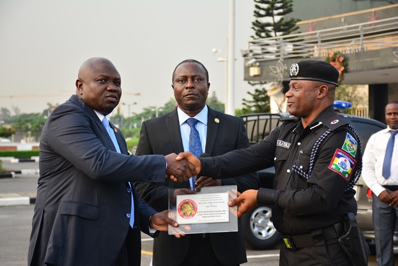 Lagos State Governor, Mr. Akinwunmi Ambode (left), being presented with the Best Security and Safety Conscious award given to the State Government in South Africa by Commander, RRS, ACP Tunji Disu (right) while Permanent Secretary, Office of Chief of Staff, Mr. Abiodun Bamgboye (middle), watches during the handing over of 3 Patrol Vehicles and 45 Power Bikes to the Rapid Response Squad (RRS) at the Lagos House, Ikeja, on Monday, December 5, 2016.