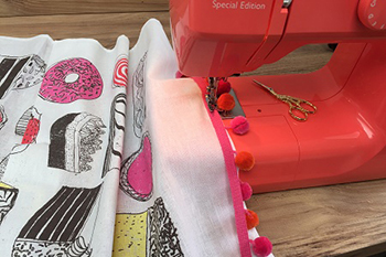 brightening up a tea towel by sewing braid