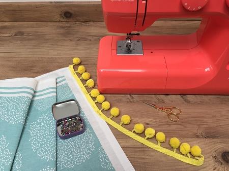 pinning pompom braid onto tea towel