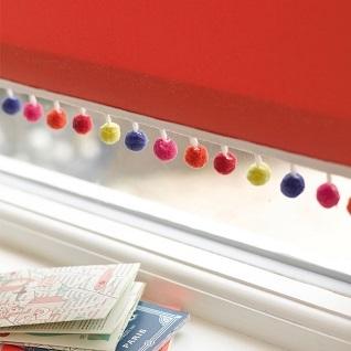 pompom braid on a red window blind