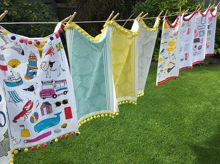 tea towels with pompom fringe on a washing line