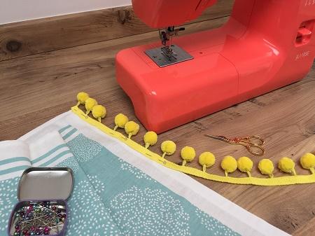 pinning pompom fringe braid onto the tea towel