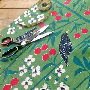 retro cherry orchard cotton fabric by the metre in green featuring cherries and blackbirds by Marian