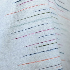 slub effect striped woven throw by Laura Fletcher in multi colour on soft grey ground