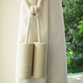 cream leather cylinder curtain tieback or hold-back in window