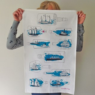 blue kitchen tea towel by illustrator charlotte farmer with blue ships-in-bottle