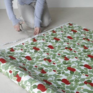 red orchard cotton print is a fresh design featuring red apples and green leaves for drapes