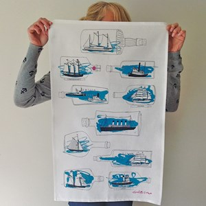blue kitchen tea towel by illustrator charlotte farmer with blue ships-in-bottle