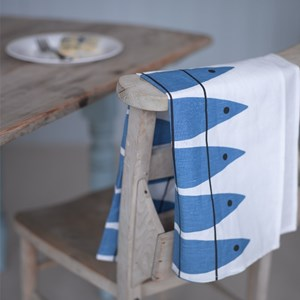 blue and white cotton/linen tea towel Swedish vintage in herring fish pattern on back of chair