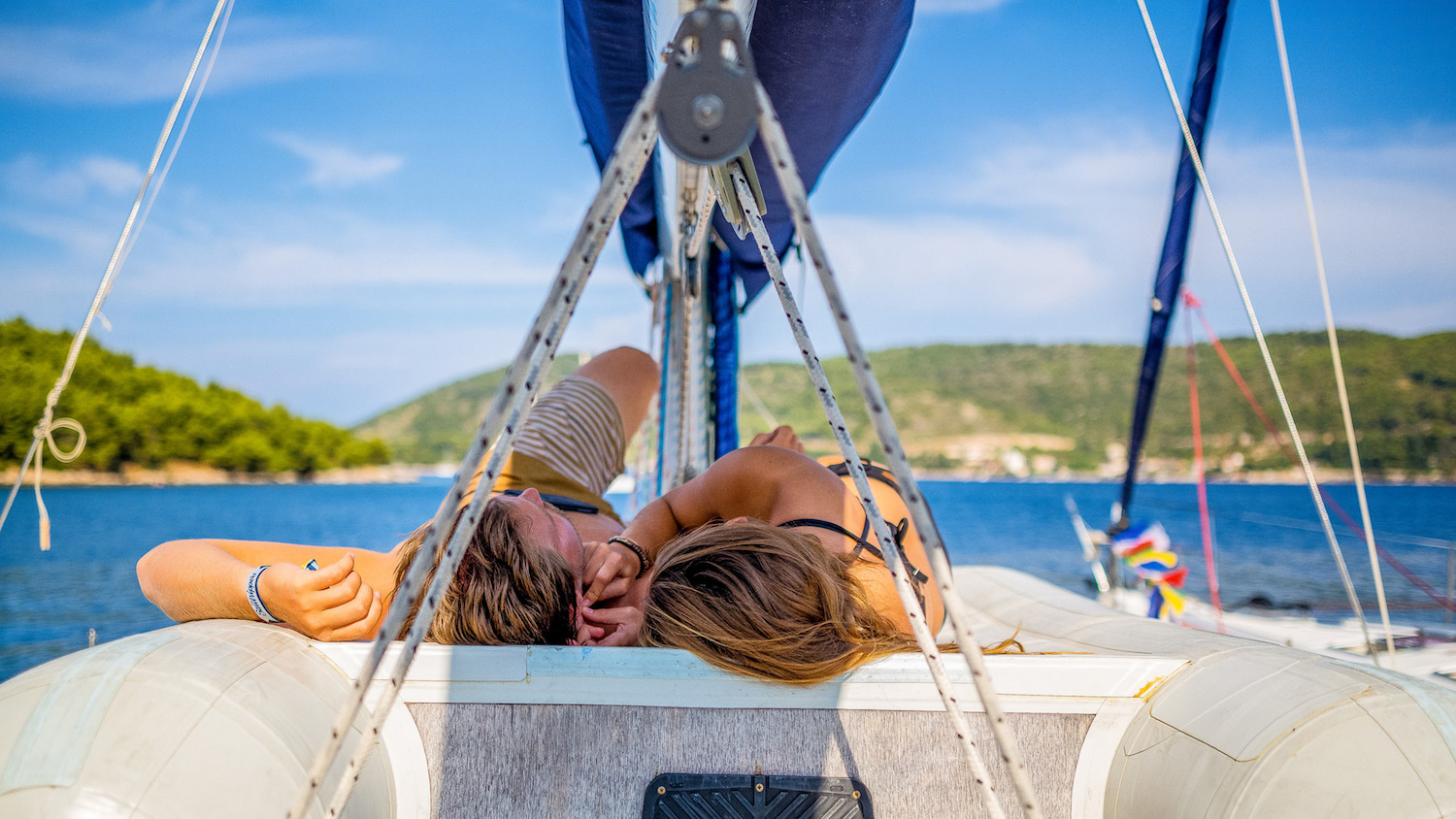 Couple on deck of a sailboat in the North Ionian Islands