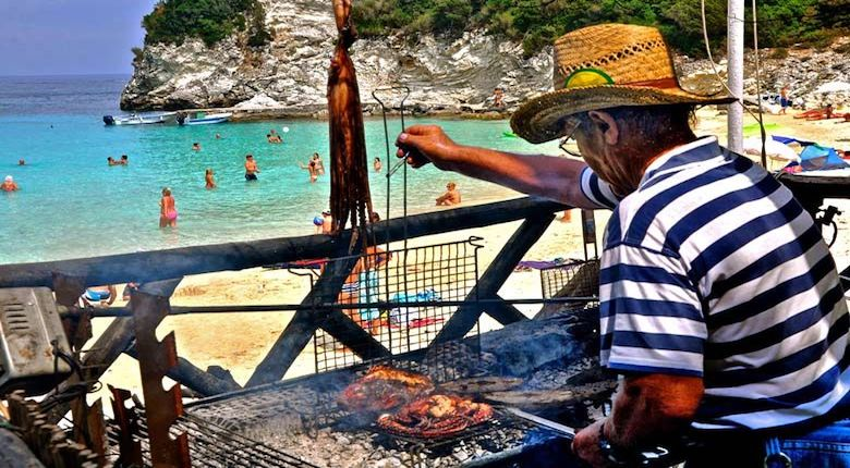 Man cooking octopus in Vrika beach, Antipaxos