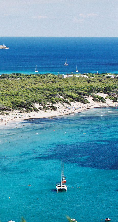 Catamaran anchored and sailboats sailing in the paradise beach of Ses Salines (Ibiza) (part 1).