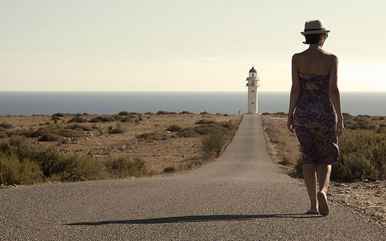 Girl walking to the lighthouse of La Mola (Formentera).